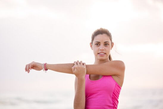woman in pink tank top stretching arm