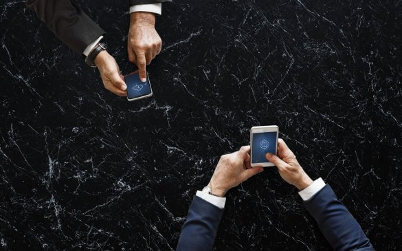 Two persons holding white and black smartphones