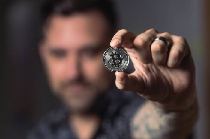 Person holding silver bitcoin
