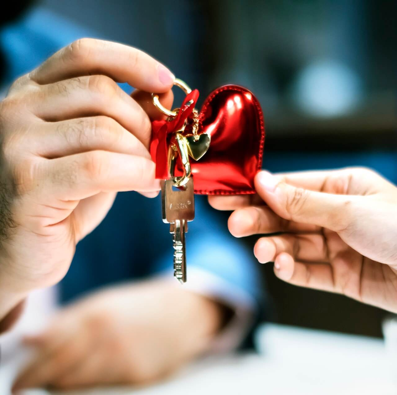 Two persons holding grey key with red heart key chain