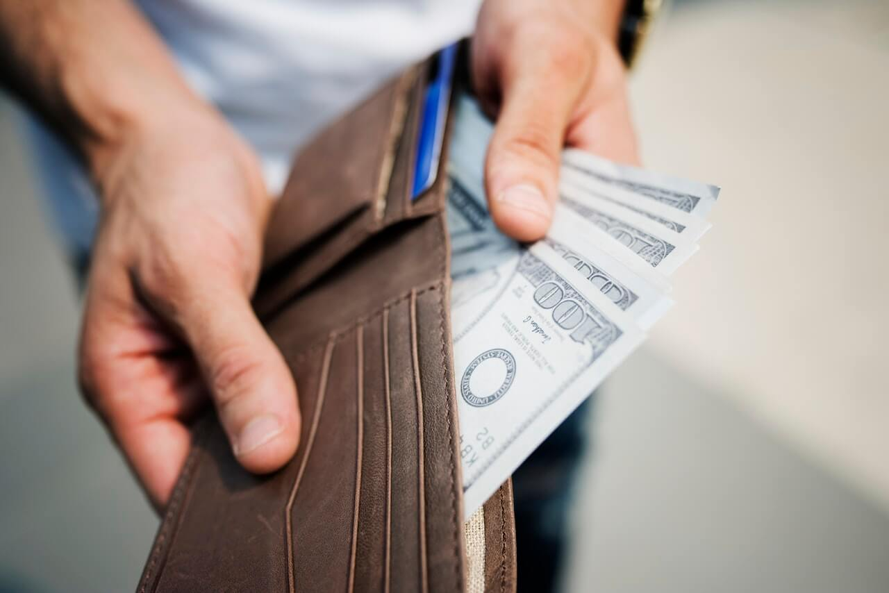 Man holding brown leather wallet with money