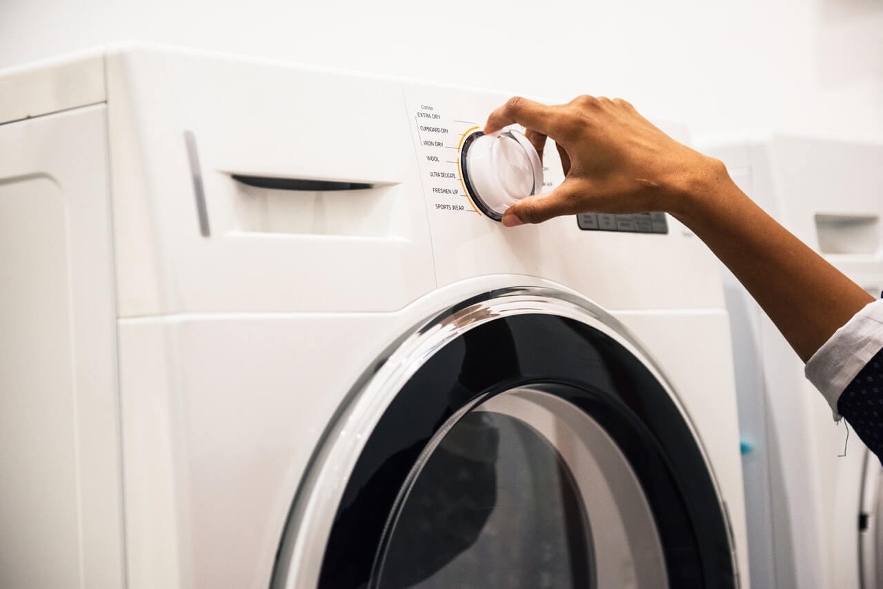 Woman adjusting control on front load washer