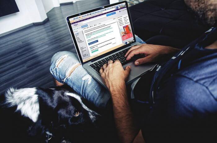Man is working on his laptop through Internet