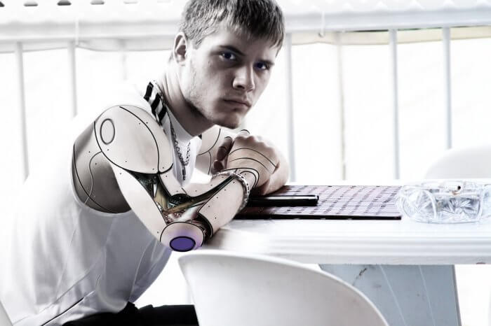 Man with artificial arm sitting infront of the table