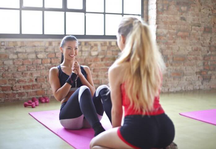 woman-with-red-top-and-black-shorts-on-purple-yoga-mat