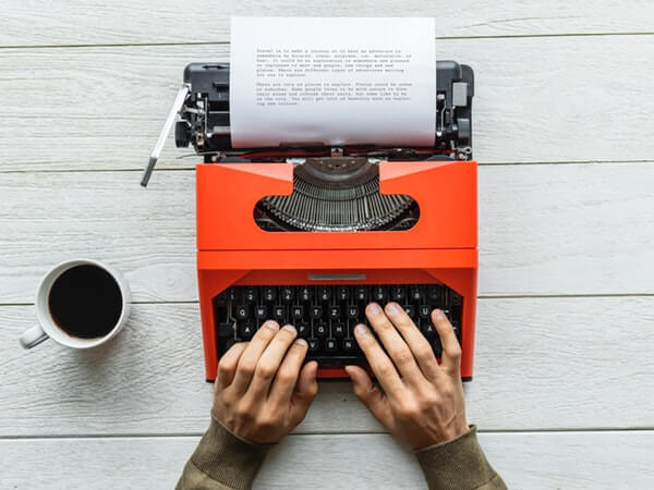 Person holding orange typewriter