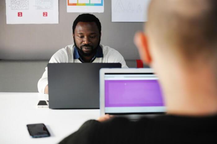 Two men sitting facing laptops