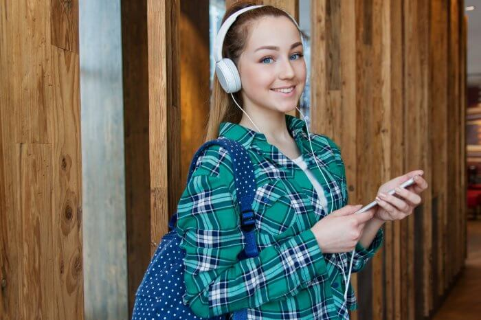 School girl standing with backpack and headphone