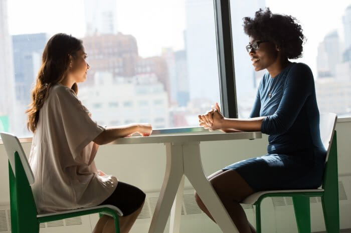 Two women sitting on Chair and having a conversation
