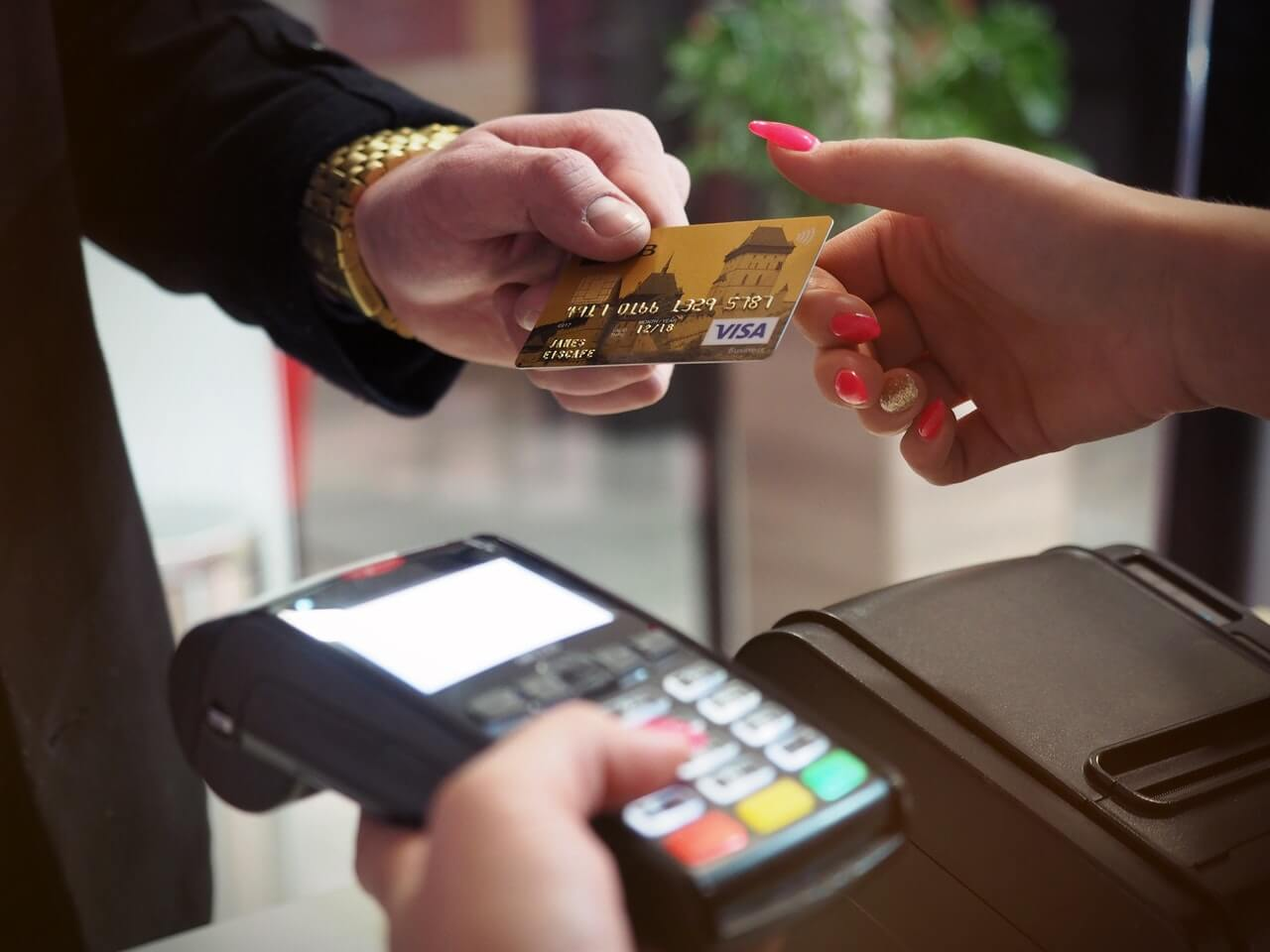 Photo of person handing credit card for payment process