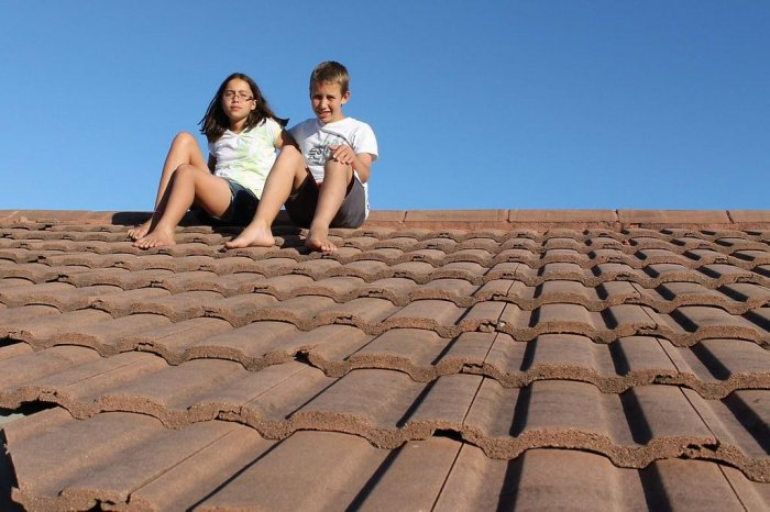 A boy and girl are sitting on a roof